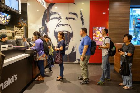 Foto de HONG KONG - OCTOBER 25, 2015: interior of McDonald's restaurant. McDonald's primarily sells hamburgers, cheeseburgers, chicken, french fries, breakfast items, soft drinks, milkshakes, and desserts - Imagen libre de derechos