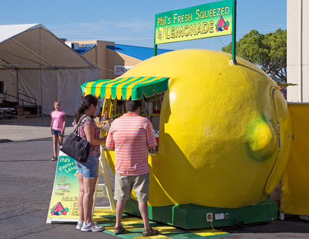 Anderson, California, USA- June 17, 2015: Customers are enjoying fresh lemonade drinks at this booth shaped like lemon at the Shasta County Fair.