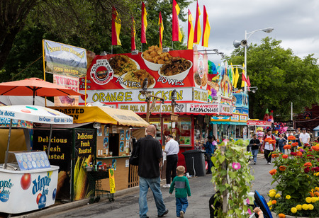 Concession stand, ticket booth, rides, and games at the county fair .