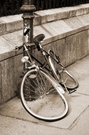 Abandoned damaged bicycle locked to an iron pillar on sidewalk  Sepia toned image