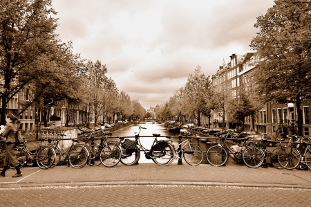 Typical view of the Amsterdam center with bicycles on a bridge across a canal in overcast spring day  Sepia toned image