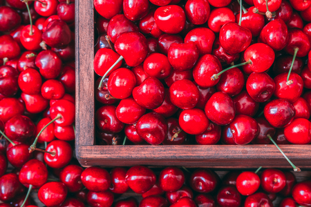Photo for Sweet cherries in the wooden box on the wooden table - Royalty Free Image