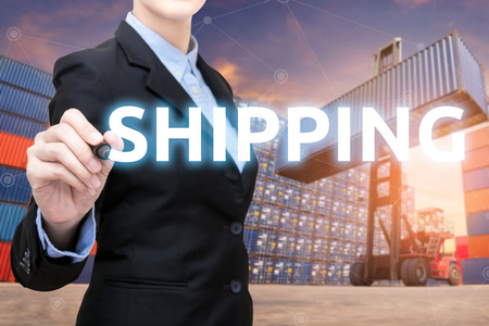 Smart Business woman is writing shipping word with cargo shipping containers in shipping yard.Photo concept for Global business shipping,Logistic,Import and Export industry.