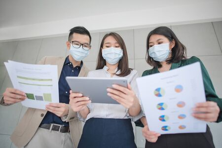 Foto de Business employees wearing mask during work in office to keep hygiene follow company policy.Preventive during the period of epidemic from coronavirus or covid19. - Imagen libre de derechos