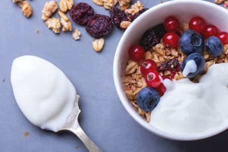 Home Made Granola breakfast with white plain yogurt, blueberries, redcurrant and dry cherries on metal background