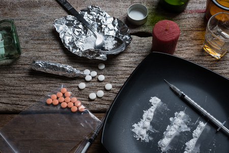 alcohol, drugs, pills on a wooden background