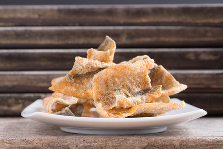 Crispy fried salmon skin on  wooden table background