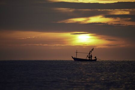 Photo pour Silhouette of a fisherman on longtail boat with sunrise and beautiful color sky - image libre de droit