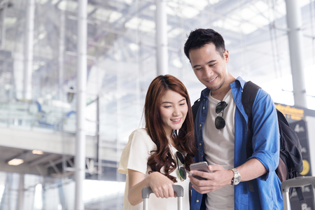 Foto de Couple asian student traveler looking or find for flight in smartphone at airport terminal. Check-in by mobile. Teenager are traveling concept. - Imagen libre de derechos