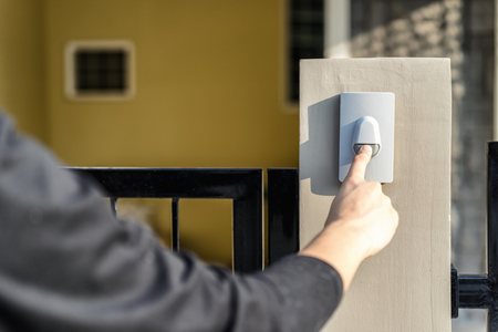 Photo pour Man's hand pressing a doorbell button with sunlight. Close up hand and finger visiter ringing buzzer doorbell. Guest press bell behind front door home. - image libre de droit