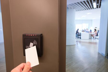 Photo for Men hand reaching to use RFID key card to access to office building area and workspace. In building security only for authorized person - Royalty Free Image