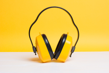 Yellow working protective headphones on yellow background