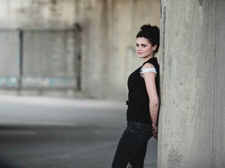 Foto de beautiful girl posing in a parking lot near the wall - Imagen libre de derechos