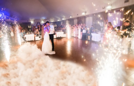Foto de beautiful bride and groom dancing the first dance between fireworks - Imagen libre de derechos