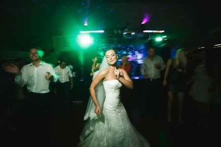 Photo pour beautiful bride and groom dancing among the people on the dance floor - image libre de droit
