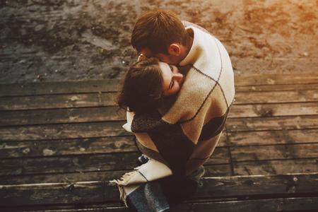 Foto de Young couple in love wrapped in plaid standing and embrace - Imagen libre de derechos