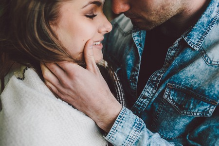 Photo pour Young couple in love wrapped in plaid standing and looking at each other - image libre de droit