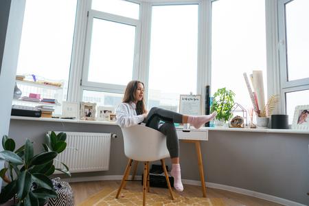 Photo pour Young woman on chair near the window - image libre de droit