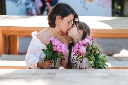 Foto de Mother and daughter kissing bouquets of peonies - Imagen libre de derechos
