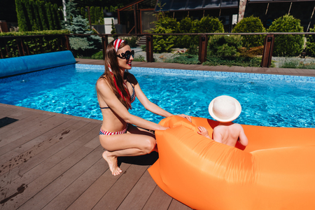 Photo pour Beauty mother with littel son by the pool - image libre de droit