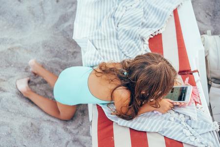 Foto de One Little girl is playing mobile phone - Imagen libre de derechos