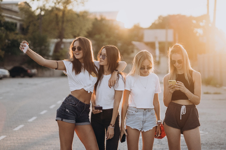 Photo pour Four young women taking a selfie and have fun - image libre de droit