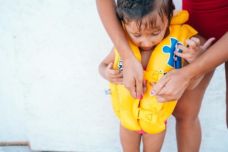 Foto de A mother helping daughter with her life jacket - Imagen libre de derechos