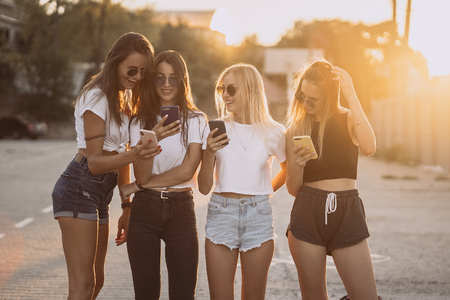 Foto de Four attractive women are standing on car parking with smartphones - Imagen libre de derechos