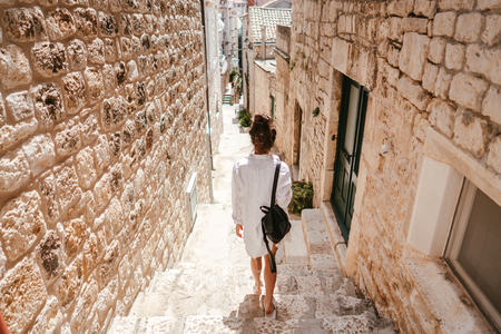 Photo pour Young girl walking through ancient narrow streets on a beautiful summer day in Croatia south Europe - image libre de droit