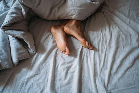 Photo pour Close-up woman feet alone in white bed - image libre de droit