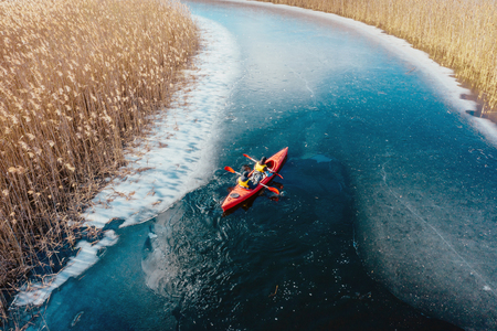 Foto de two athletic man floats on a red boat in river - Imagen libre de derechos