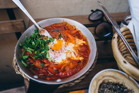 Photo for Shakshuka, Fried Eggs in Tomato Sauce on the Table - Royalty Free Image