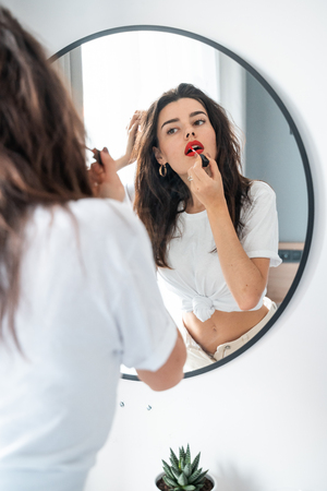 Foto de Young woman applying lipstick looking at mirror - Imagen libre de derechos