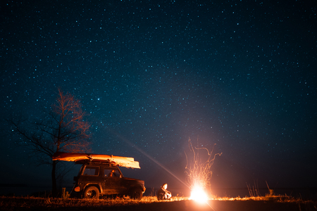 Photo for Happy man sitting in front burning bonfire - Royalty Free Image