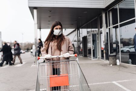 Photo pour Young woman wearing protection face mask against coronavirus 2019-nCoV pushing a shopping cart. - image libre de droit