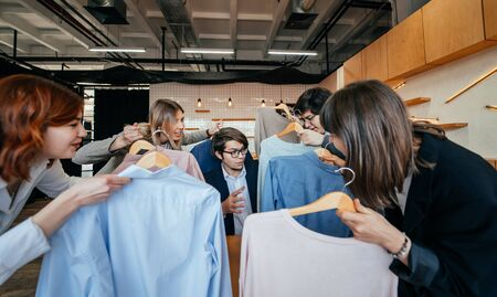 Photo pour Young stylist looking through set of shirts for fashion shooting - image libre de droit