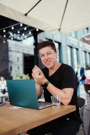 Photo pour Portrait of man sitting at a table working on a laptop computer. - image libre de droit