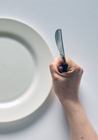 Fork and knife in hands on white background with white plate