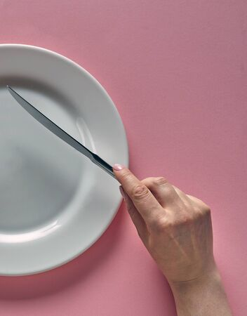 Fork and knife in hands on rose background with white plate.