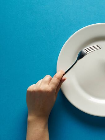 Fork and knife in hands on blue color background with white plate