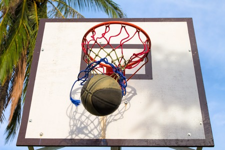 Basketball sport equipment. Ball and basket activity. Summer outdoor sport game. Active lifestyle during school holiday. Throwing ball to basket. Basketball competition. Sunny weather day outside