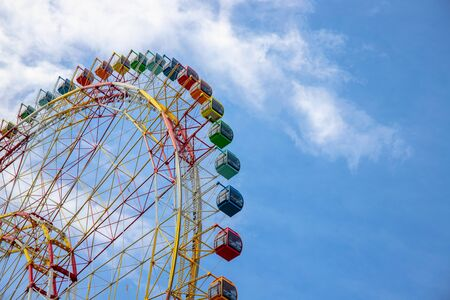 Photo pour Ferris wheel on blue sky background. Ferris wheel attraction in summer park. Orange metallic construction of attraction. Colorful car on ferris wheel. Summer holiday in adventure park. Kids weekend - image libre de droit