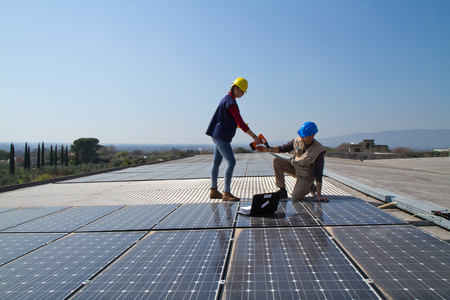 Photo pour young engineer girl and an elderly skilled worker fitting a photovoltaic plant - image libre de droit