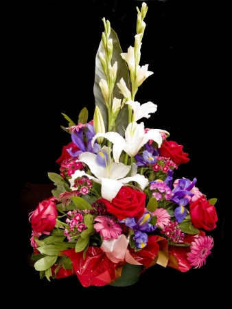 Different flowers bouquet in a basket, isolated in black