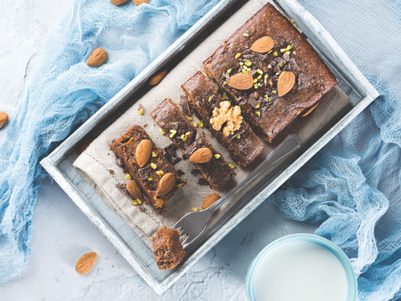 Chocolate cake with persimmons, almonds and nuts on wooden tray for cozy breakfast with mug of milk. Gray and blue winter pastel colors. Top view