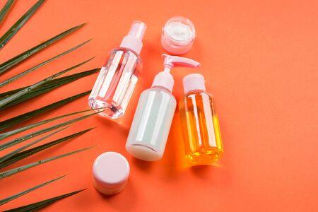 Foto de Generic beauty products on orange coral background. Summer travel kit or sun protection concept. - Imagen libre de derechos