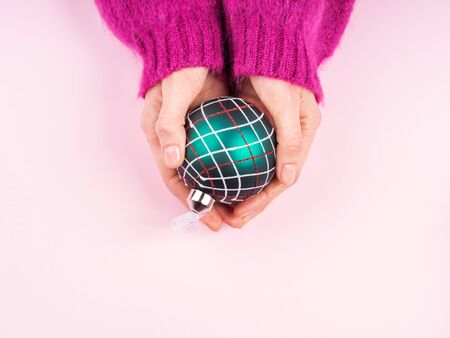 Photo for Womans hand in cozy sweater holding christmas green and red ornament bauble sphere on pink background. Festive concept - Royalty Free Image