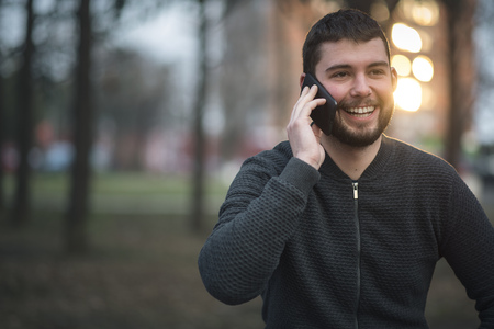 Young mid-twenties man talking on his cell phone, speaking with a friend as hes taking a walk in a park