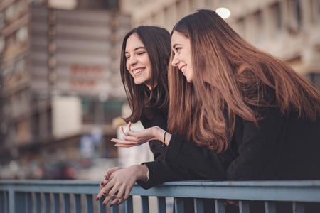 Photo pour Two beautiful girls on the street having a small chat, enjoying a walk - image libre de droit