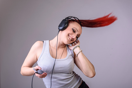 Young funky modern dancer dancing to the rhythm of the music shes listening on her phone, happy and cheerful, red fiery hair tied in a pony tail